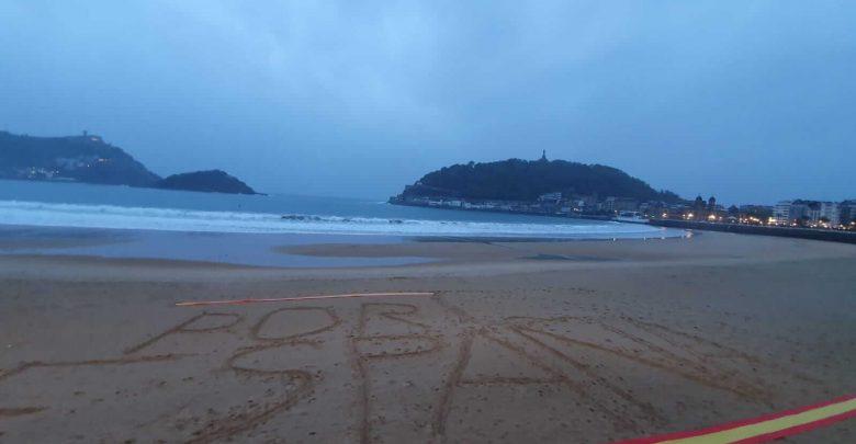 Photo of La playa de la Concha, amanece con una gran bandera española sobre la arena
